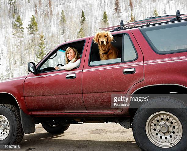 Woman and dog in dirt splattered SUV looking out windows in snowy countryside