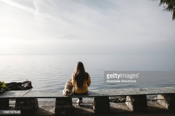 woman and dog looking at foggy mountains and lake geneva in montreux - montreux stock pictures, royalty-free photos & images