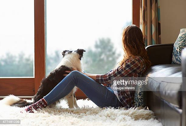 Woman and dog looking out of window.