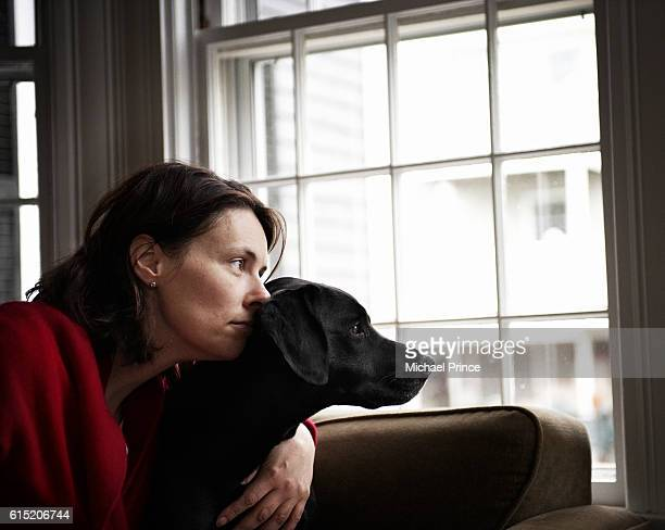 woman and dog looking out window - labrador preto imagens e fotografias de stock