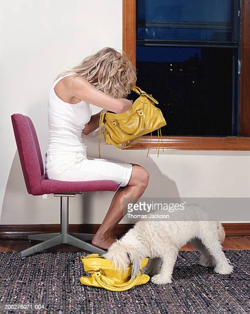 Woman and dog looking through matching handbags, side view