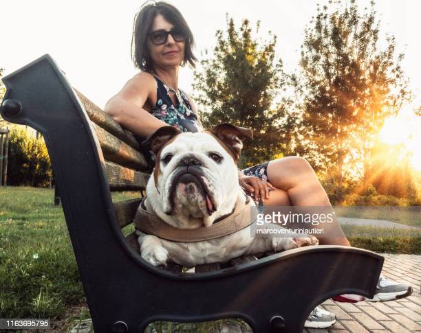 woman and dog on a bench in the park - marcoventuriniautieri stock pictures, royalty-free photos & images