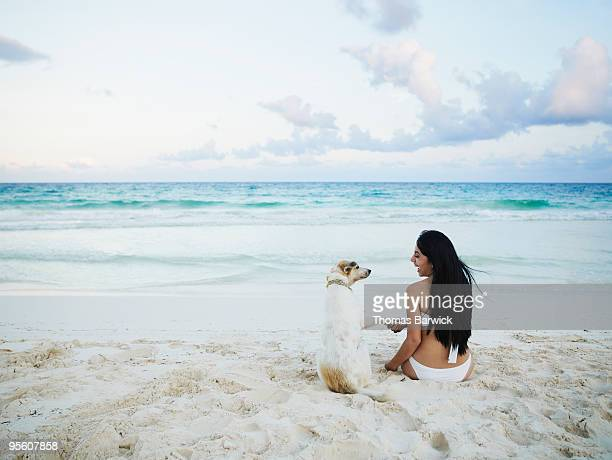 Woman and dog on beach together shaking hands