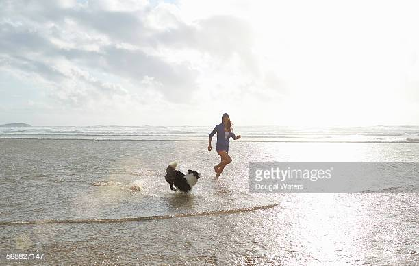 Woman and dog playing at beach.