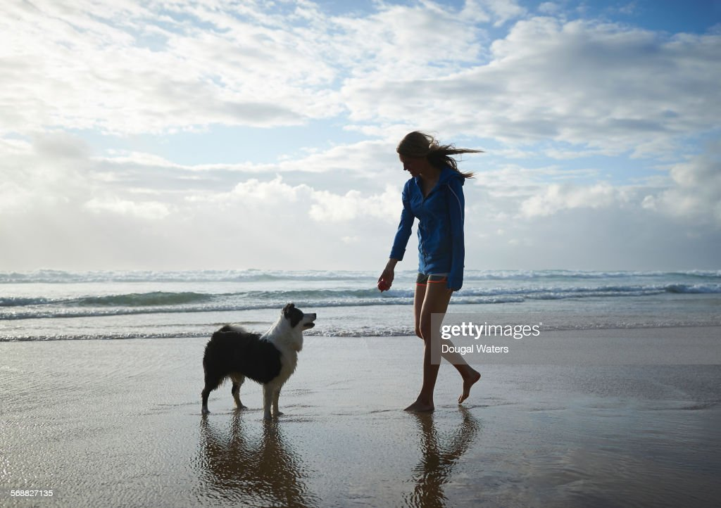 Woman and dog playing ball at beach. : Stock Photo