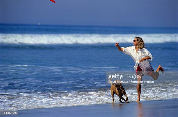 Woman and Dog Playing with Plastic Discus