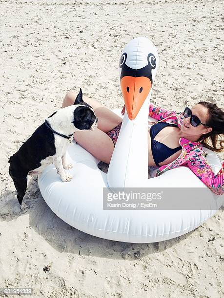 Woman And Dog Relaxing On Beach