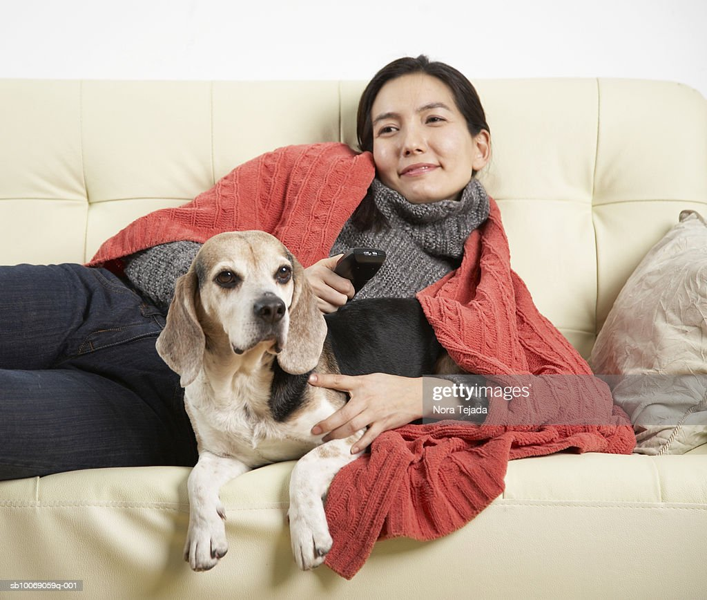 Woman and dog relaxing on sofa : Stockfoto
