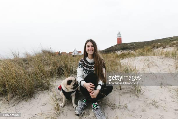 de vrouw en de hond zitten dichtbij rode vuurtoren bij het strand van het zandduin op telex eiland - noord holland stockfoto's en -beelden
