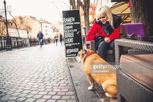 女性とドッグシッターサービスには、サイドウォークカフェ」の屋外