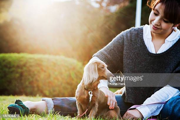 woman and dog sitting in the park
