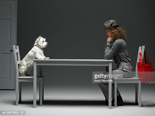 Woman and dog sitting on chair at table, face to face, side view