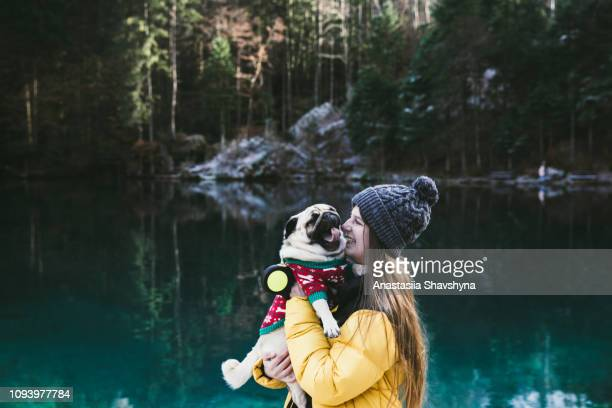 woman and dog walking at lake blausee in switzerland - blue jacket stock pictures, royalty-free photos & images