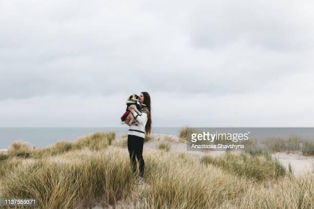 vrouw en hond wandelen op zandduin strand op texels eiland - noord stockfoto's en -beelden