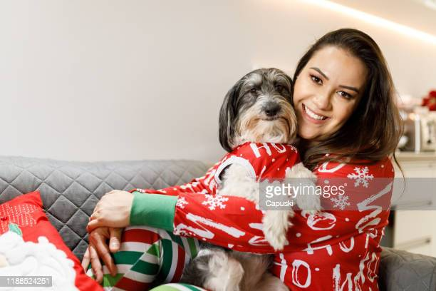 woman and dog wearing christmas pajamas - pet clothing stock pictures, royalty-free photos & images
