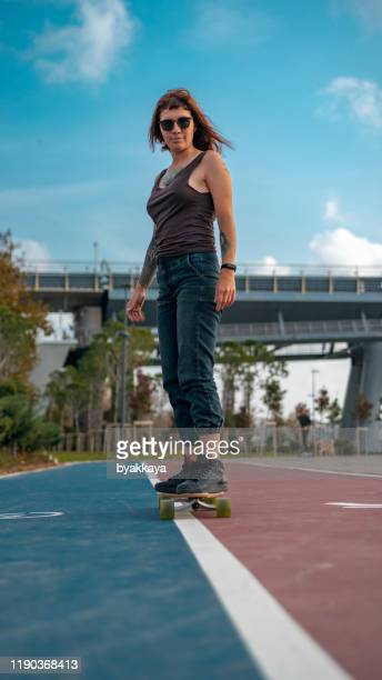 woman and driving longboards - longboard skating stock pictures, royalty-free photos & images
