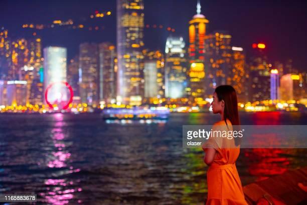 vrouw en beroemde hong kong cityscape bezienswaardigheid uitzicht - victoria harbour hong kong stockfoto's en -beelden