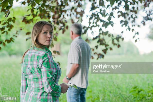 Woman and father standing in grass