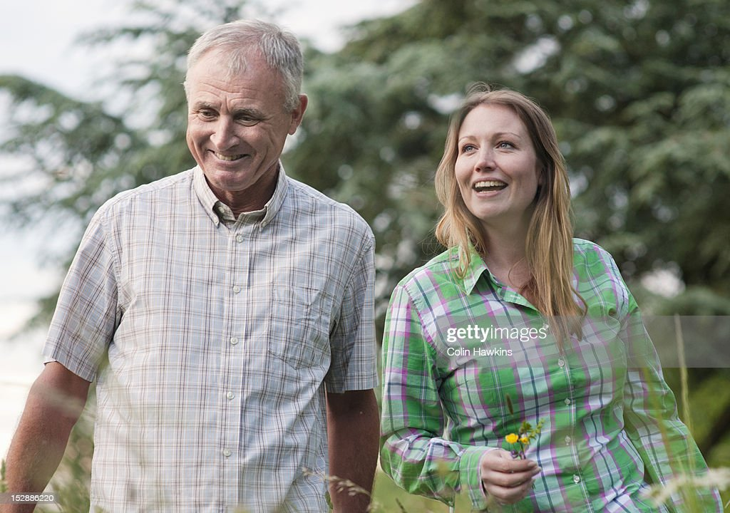 Woman and father walking outdoors : Stock Photo