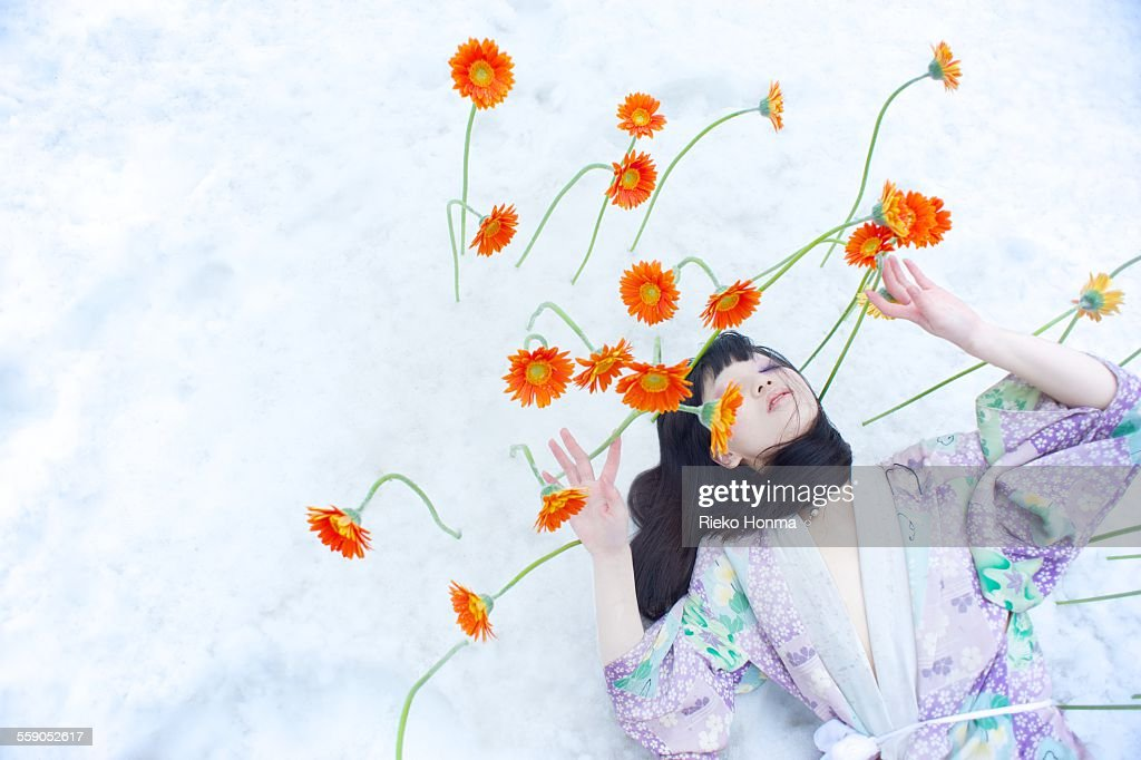 Woman and flowers bloom on top of the snow : ストックフォト