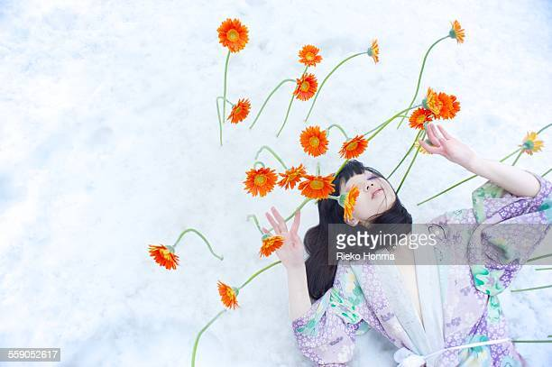 Woman and flowers bloom on top of the snow
