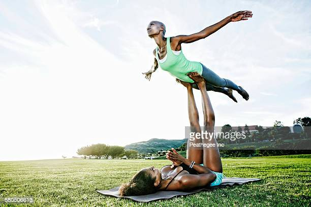 Woman and friend practicing acro yoga in park