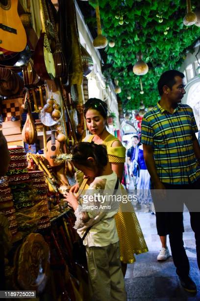 woman and girl at a night market in urumqi - sergio amiti stock pictures, royalty-free photos & images