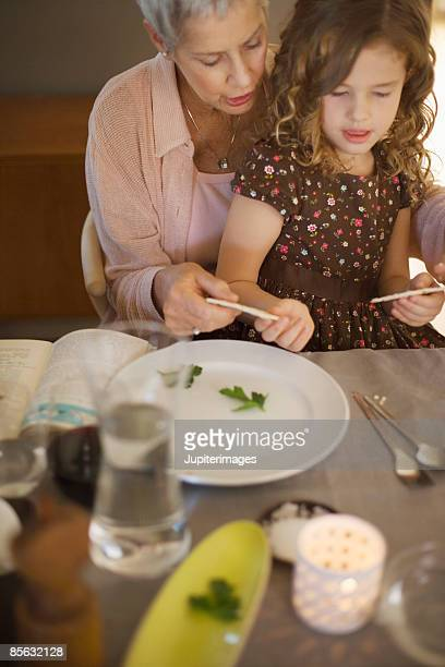 Woman and girl breaking matzoh during seder ritual