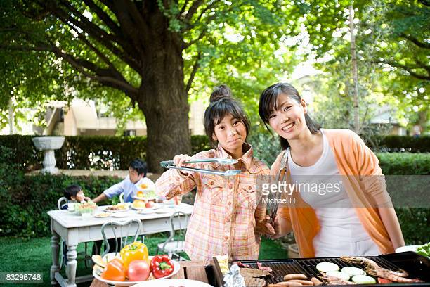 Woman and girl cooking barbecue for family in yard