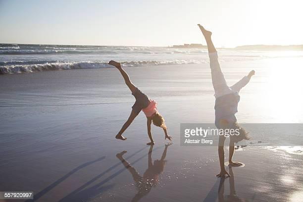 Woman and girl doing cartwheels on beach