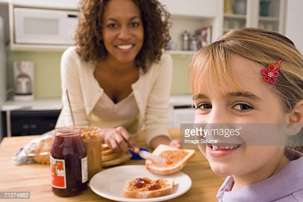 Woman and girl eating in kitchen