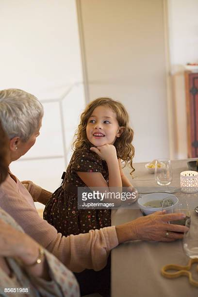 Woman and girl engaged in conversation at dinner table