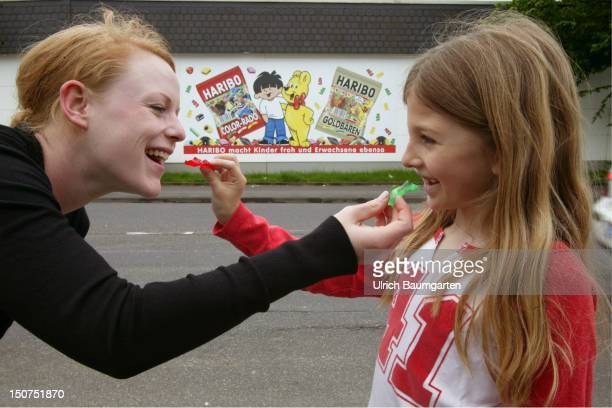 Woman and Girl feed someone with jelly bears behind their adverteising of Haribo