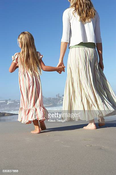 Woman and girl holding hands