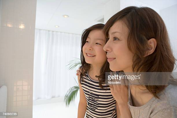 Woman and girl in bathroom, Looking into mirror