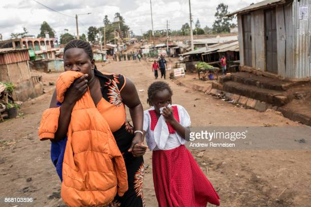 A woman and girl look scared as they walk past police after tear gas was fired in the Kawangware slum on October 30 2017 in Nairobi Kenya Tensions...