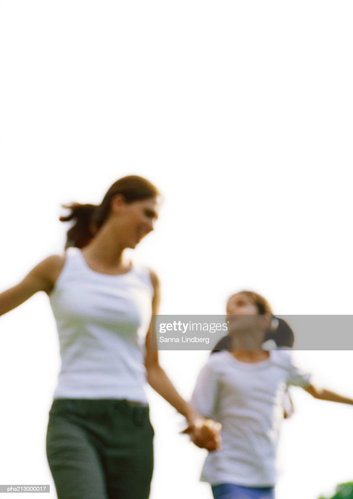 Woman and girl looking at each other and holding hands, blurred motion : Stockfoto
