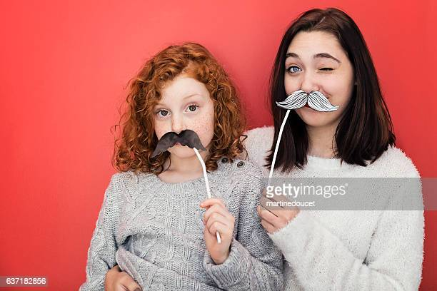 Woman and girl making faces with props mustaches, red wall.