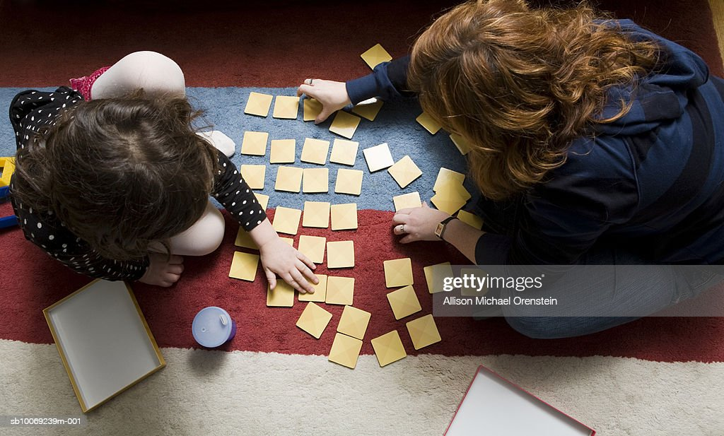 Woman and girl (4-5) playing memory game, directly above : Stockfoto