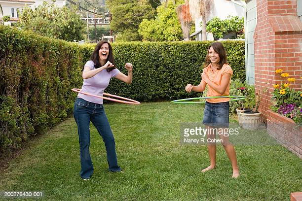Woman and girl (11-13) playing with plastic hoops in yard, portrait