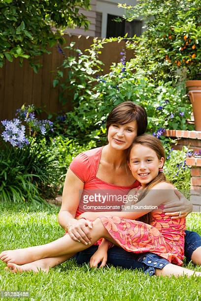 Woman and girl sitting on grass smiling