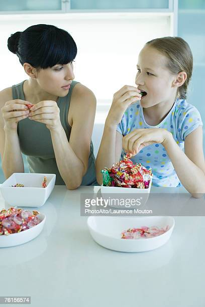 woman and girl sitting side by side eating bowls of candy - bowl of candy stock photos and pictures