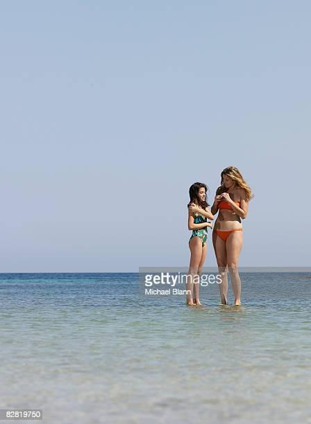 Frau und Mädchen stand in das Meer