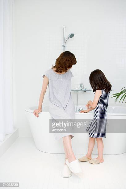 woman and girl talking in bathroom - fille sous la douche photos et images de collection