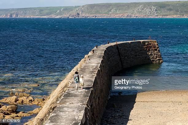 Woman and girl walking on breakwater quay Sennen Cove Land's End Cornwall England UK