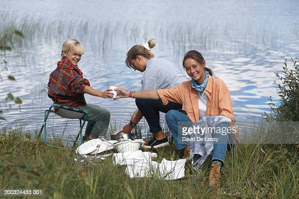 Woman and girl (6-7) washing utensils by lake