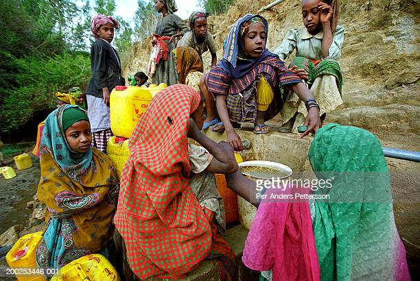 woman and girls fetch water in rural village in erer valley, ethiopia - per-anders pettersson stock pictures, royalty-free photos & images