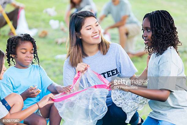 Woman and girls pick up trash in park