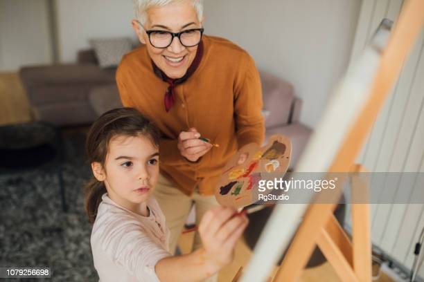 woman and granddaughter painting - human relationship stock pictures, royalty-free photos & images
