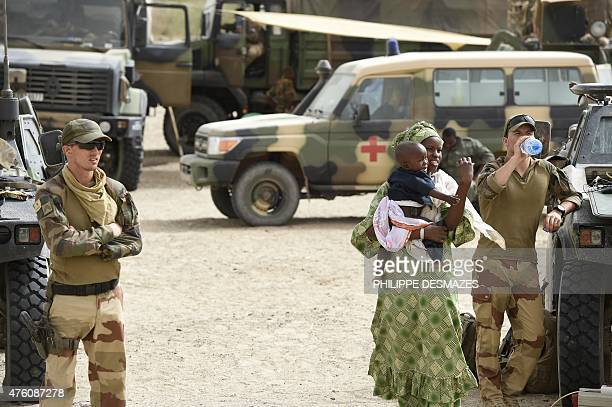 A woman and her baby arrive for medical attention provided by the French and Malian armies on June 5 2015 at M'Bouna in Timbuktu region northern Mali...